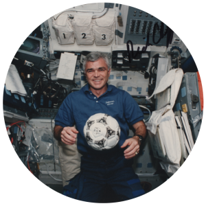 Rich Clifford, smiling man in a spaceship with a soccer ball floating in front of him.